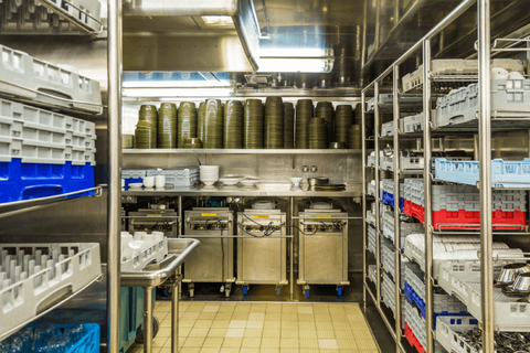 A section of the commercial kitchen where dishwashing and inventory are managed by kitchen staff.